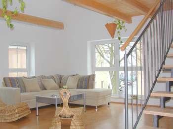 komfortables Wohnzimmer im Ferienhaus mit Couchgarnitur und Musikanlage, Treppe zur Galerie und den Schlafzimmern