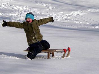 winterurlaub-bayern-schlittenfahren-kind-spass